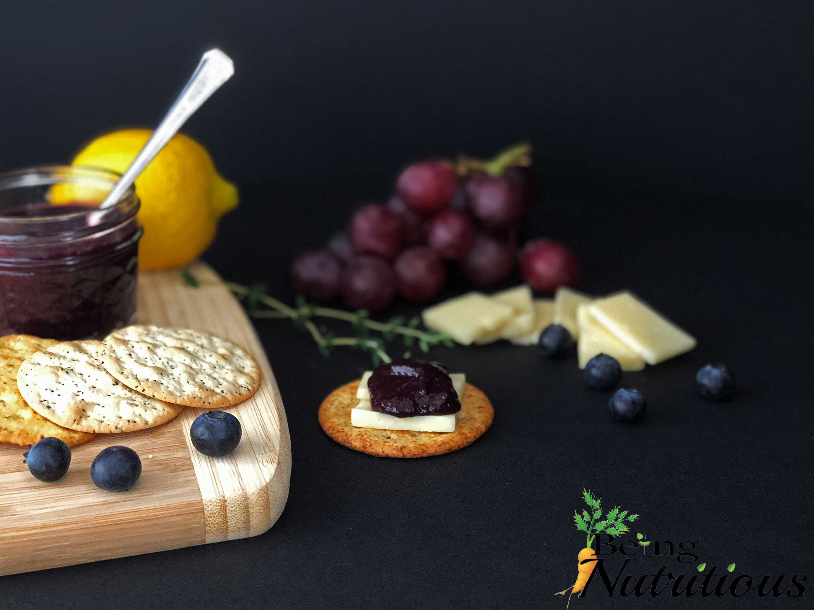 Blueberry Thyme Chia Jam on cracker with cheese.