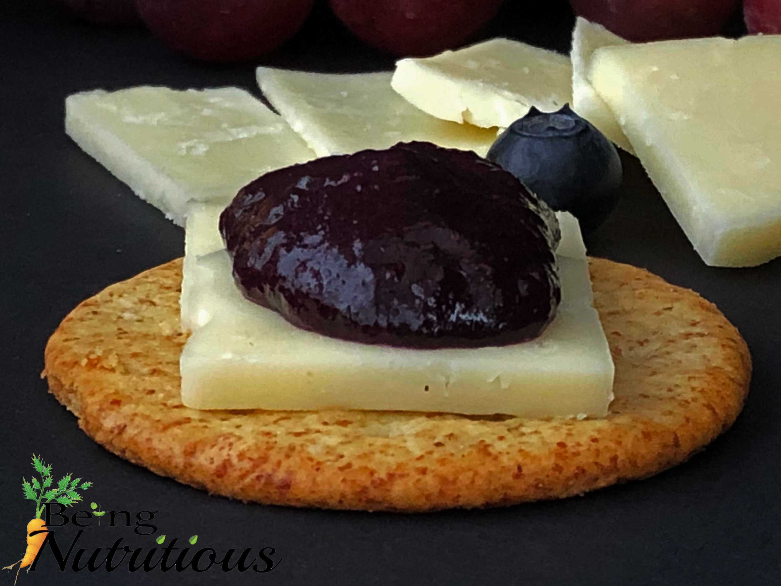 Close up of blueberry thyme chia jam with cheese on cracker.