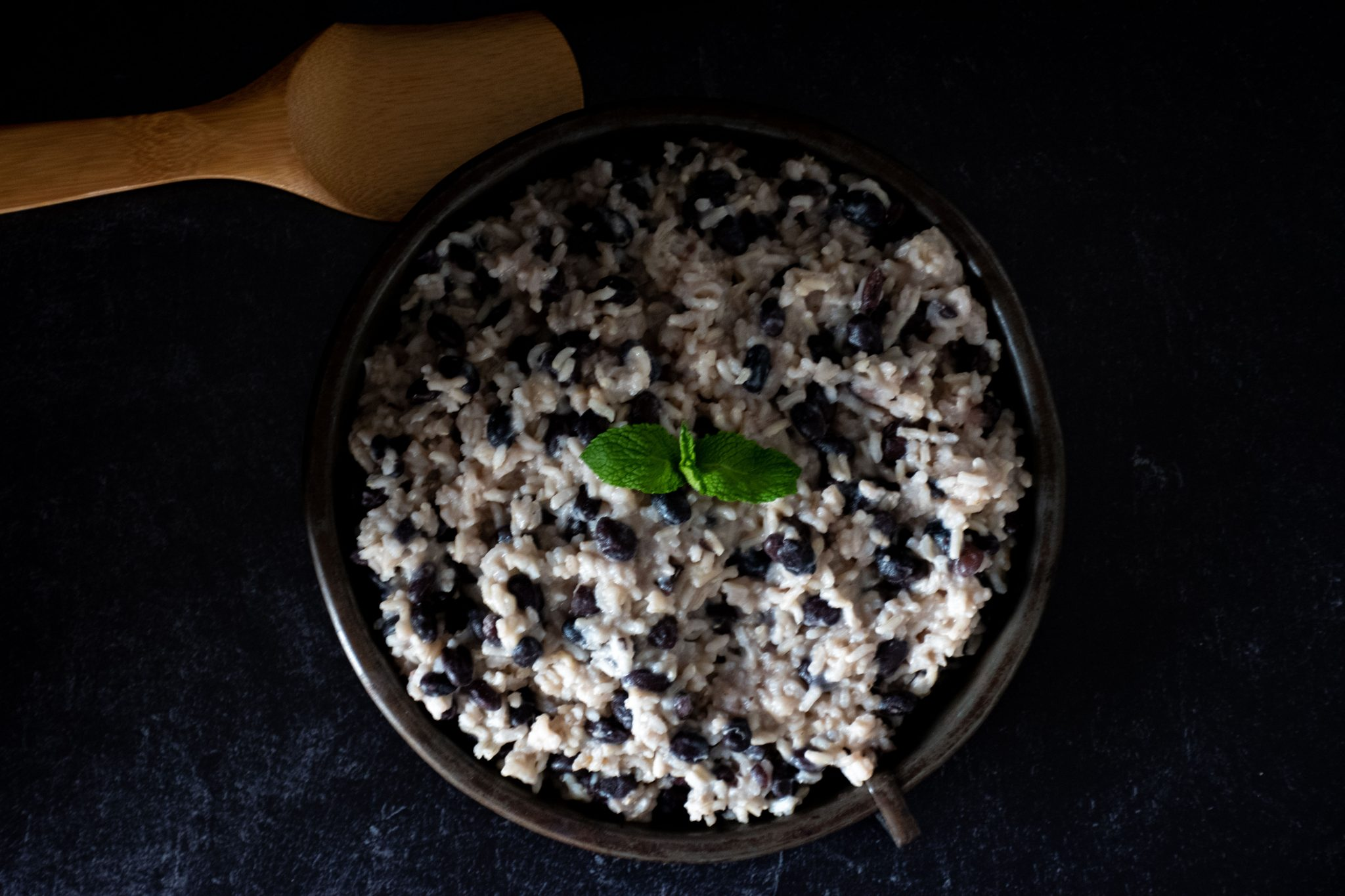 Banana coconut rice and black beans on a round metal plate, garnished with mint, on a dark background with dramatic shadows.
