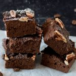 Fudgy Mocha Black Bean Brownies with powdered sugar being sprinkled on them