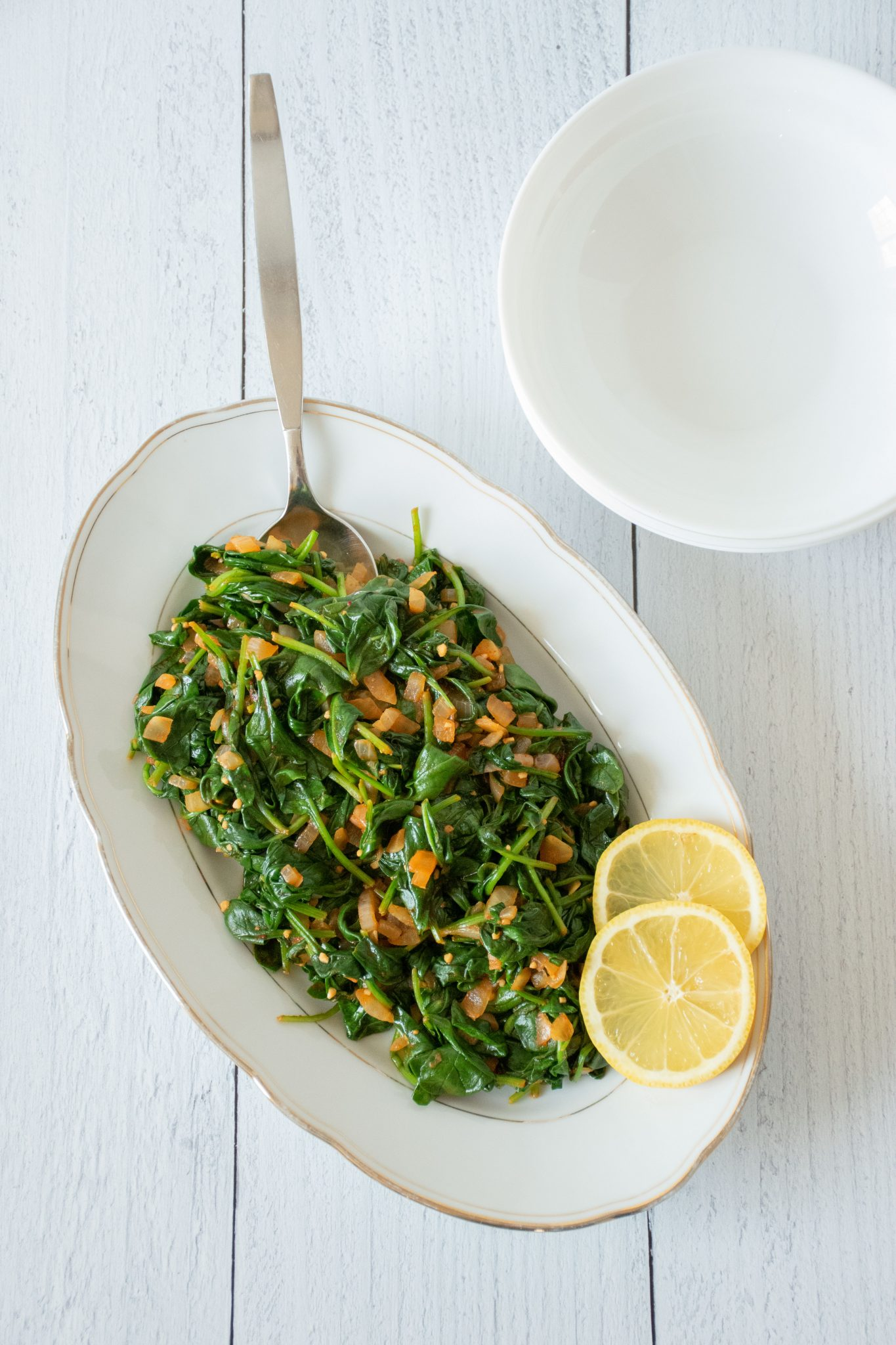 Top view of Smoky Sauteed Spinach, with a spoon in the dish and 2 lemon slices on the side.