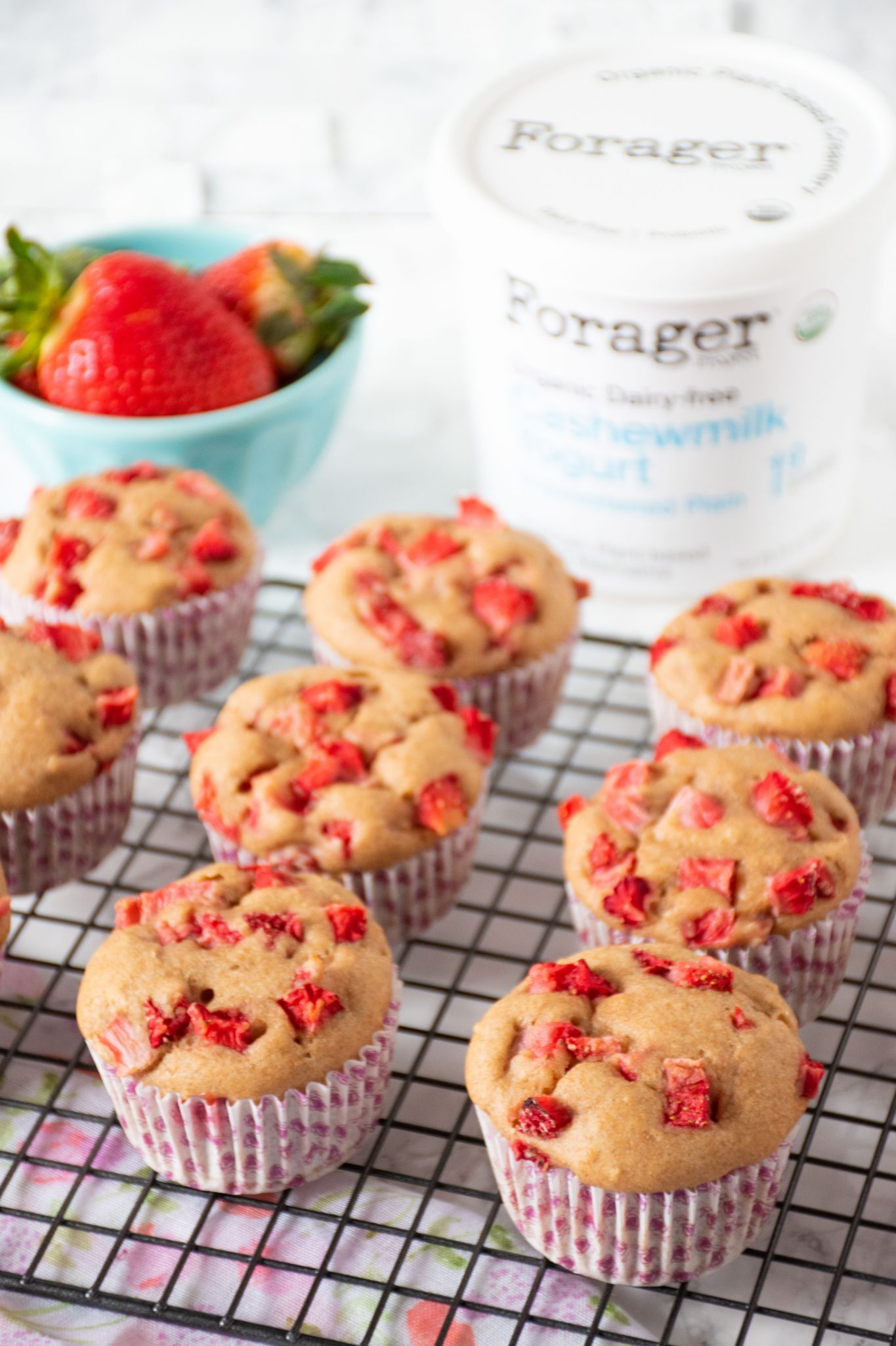 Strawberry muffins on a wire rack with a small bowl of strawberries and Forager Cashewmilk Yogurt in the background