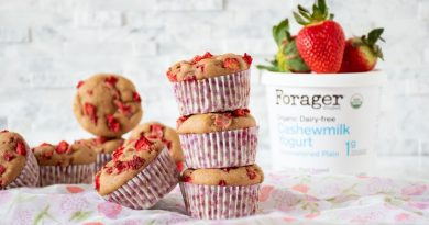 Stack of 3 strawberry muffins with one leaning against the stack, and Forager Cashewmilk Yogurt in background