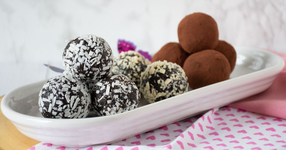 Plate of chocolate date truffles covered in shredded coconut, almond pieces, and cocoa powder