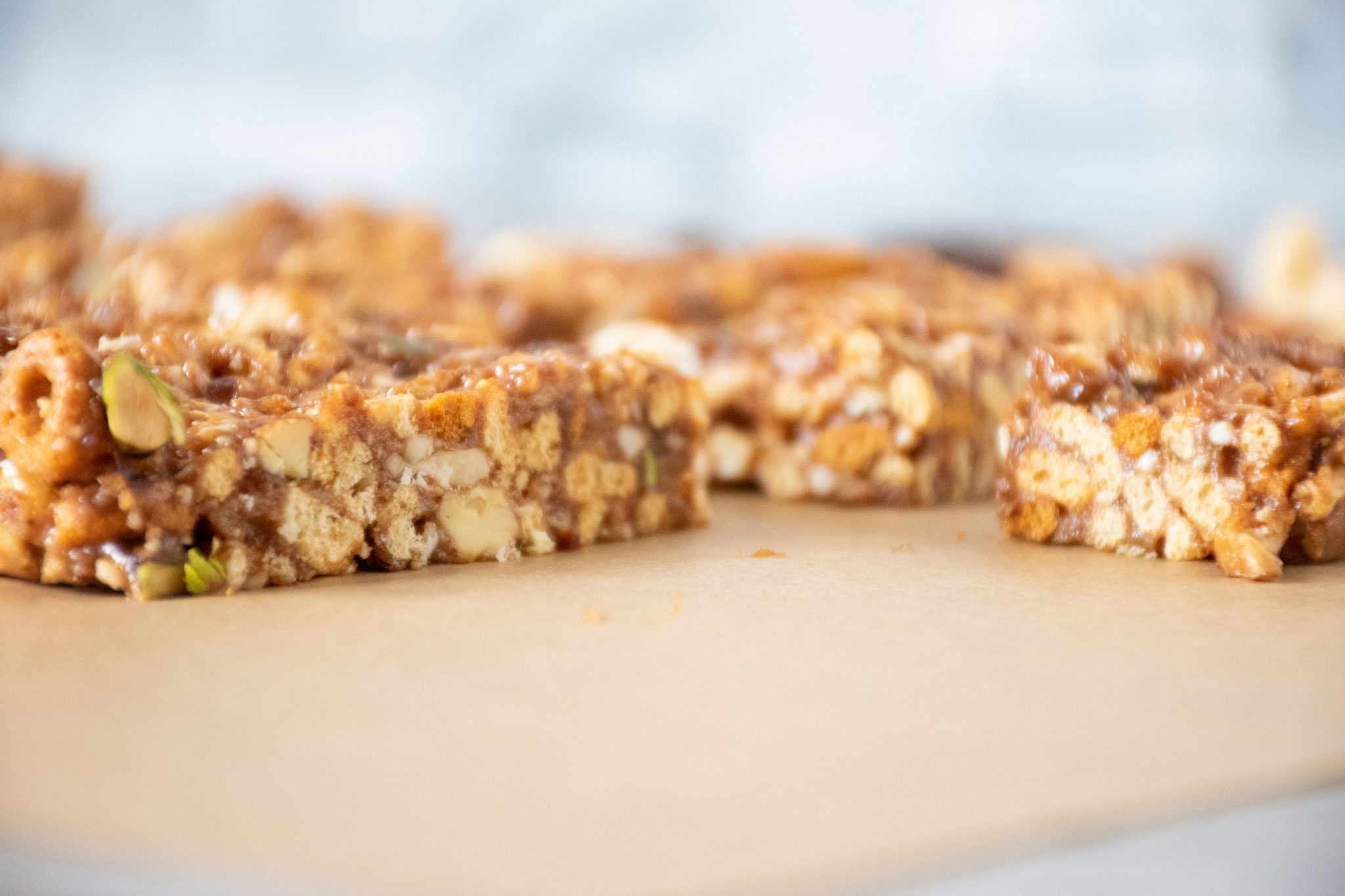 Close up of the side of cereal bars, on parchment paper.