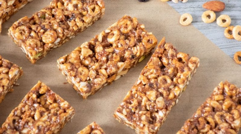 Peanut Butter Cereal Bars lined up on parchment paper