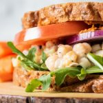 Everything Bagel Chickpea Salad Sandwich with tomato, onion, and lettuce.