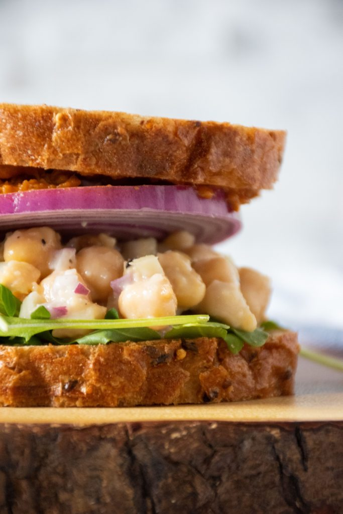 Everything Bagel Chickpea Salad Sandwich with red onion.