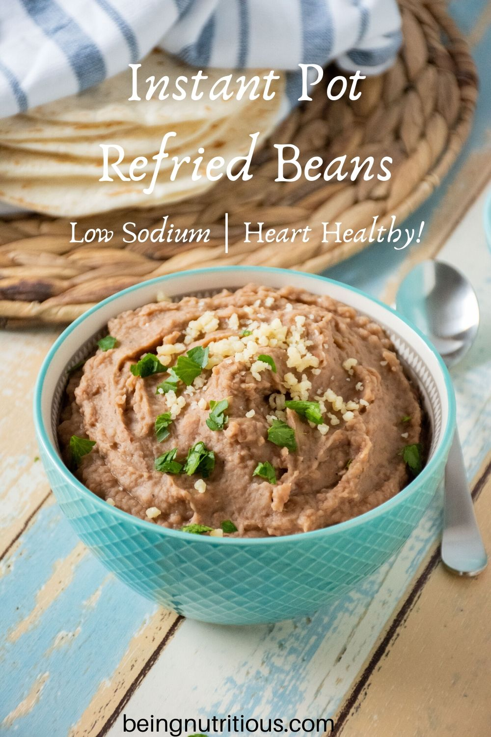 Bowl of refried beans with tortillas in the background.