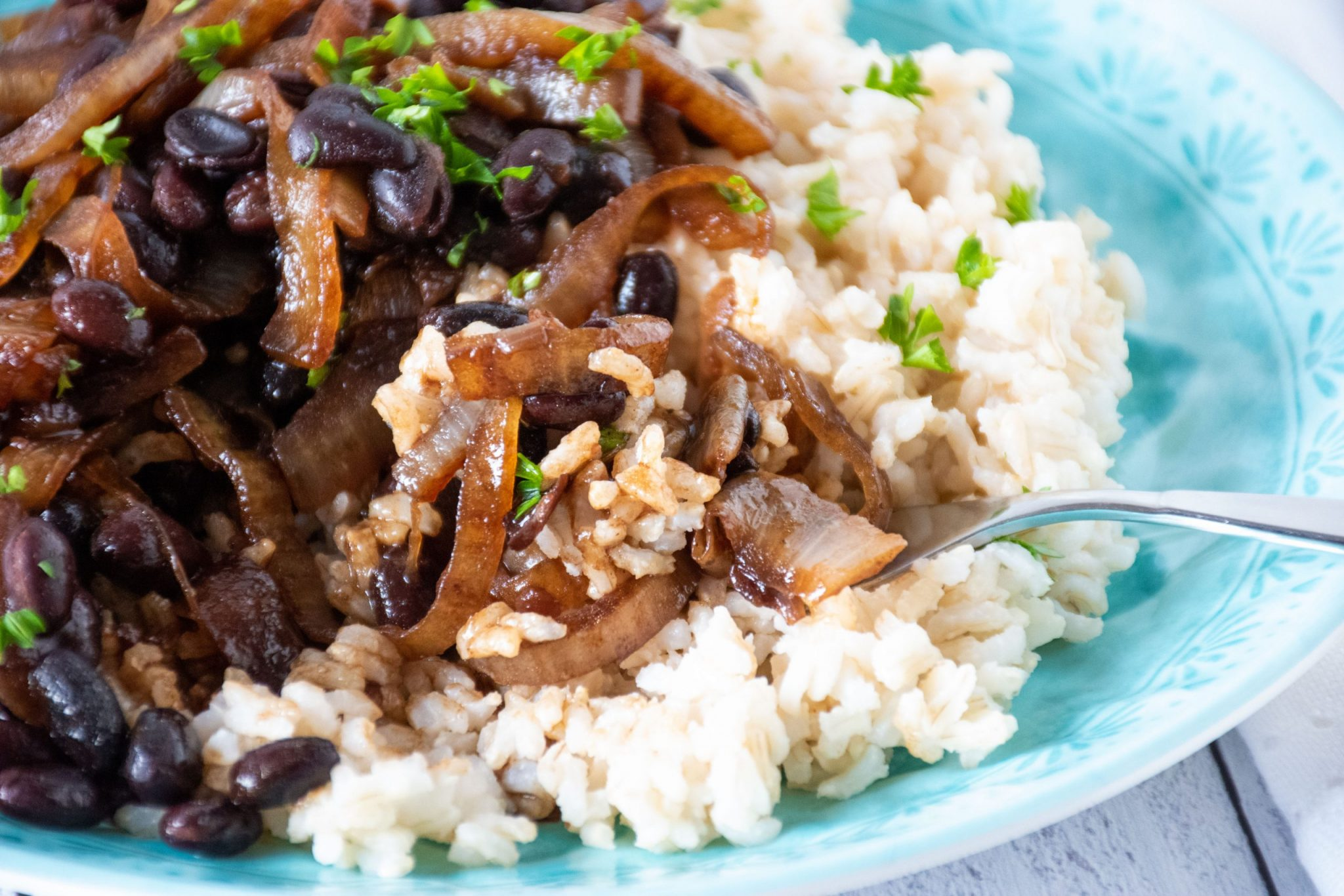 Close up of Balsamic glazed onions and black beans on a blue plate, with a fork.