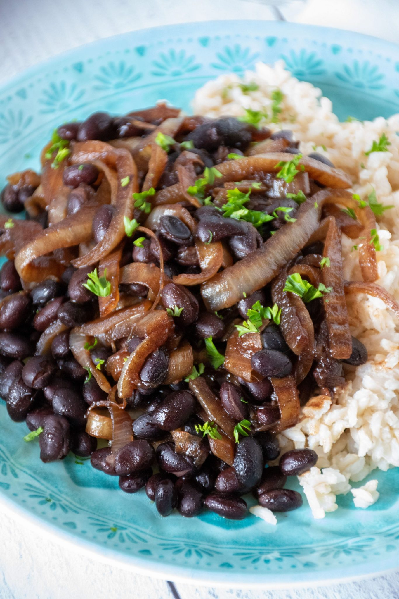 Balsamic glazed onions and black beans with rice on a blue plate, garnished with chopped parsley.