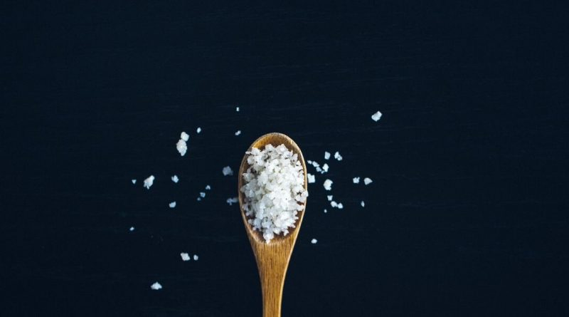 wooden spoonful of salt on a black background