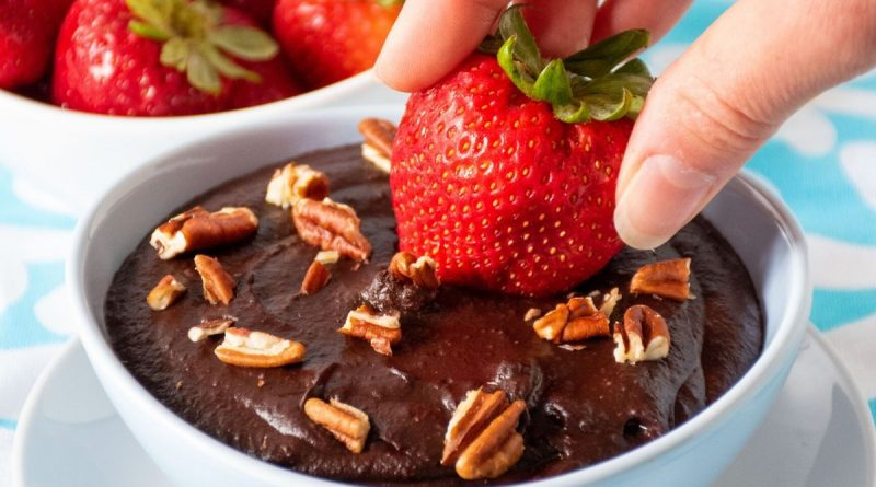 Strawberry being dipped into a bowl of brownie batter dip.