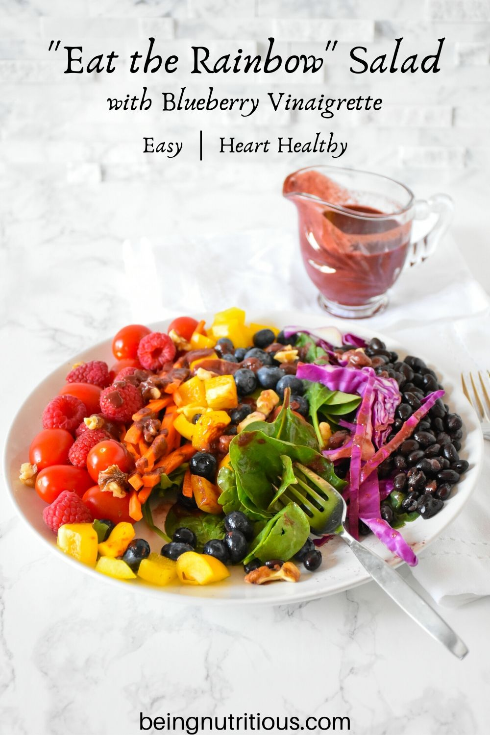 Rainbow salad on a plate, with blueberry vinaigrette dressing poured on, and several bites take from salad.