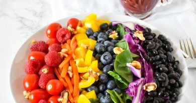 Plate of rainbow salad, ingredients arranged by color, and a glass vessel of blueberry vinaigrette dressing in the background.