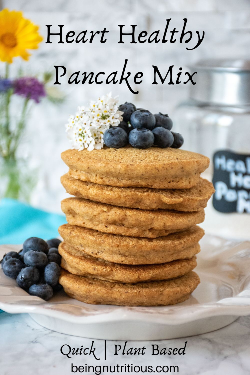 Stack of 6 whole wheat pancakes, with a pile of fresh blueberries and white flowers on top.