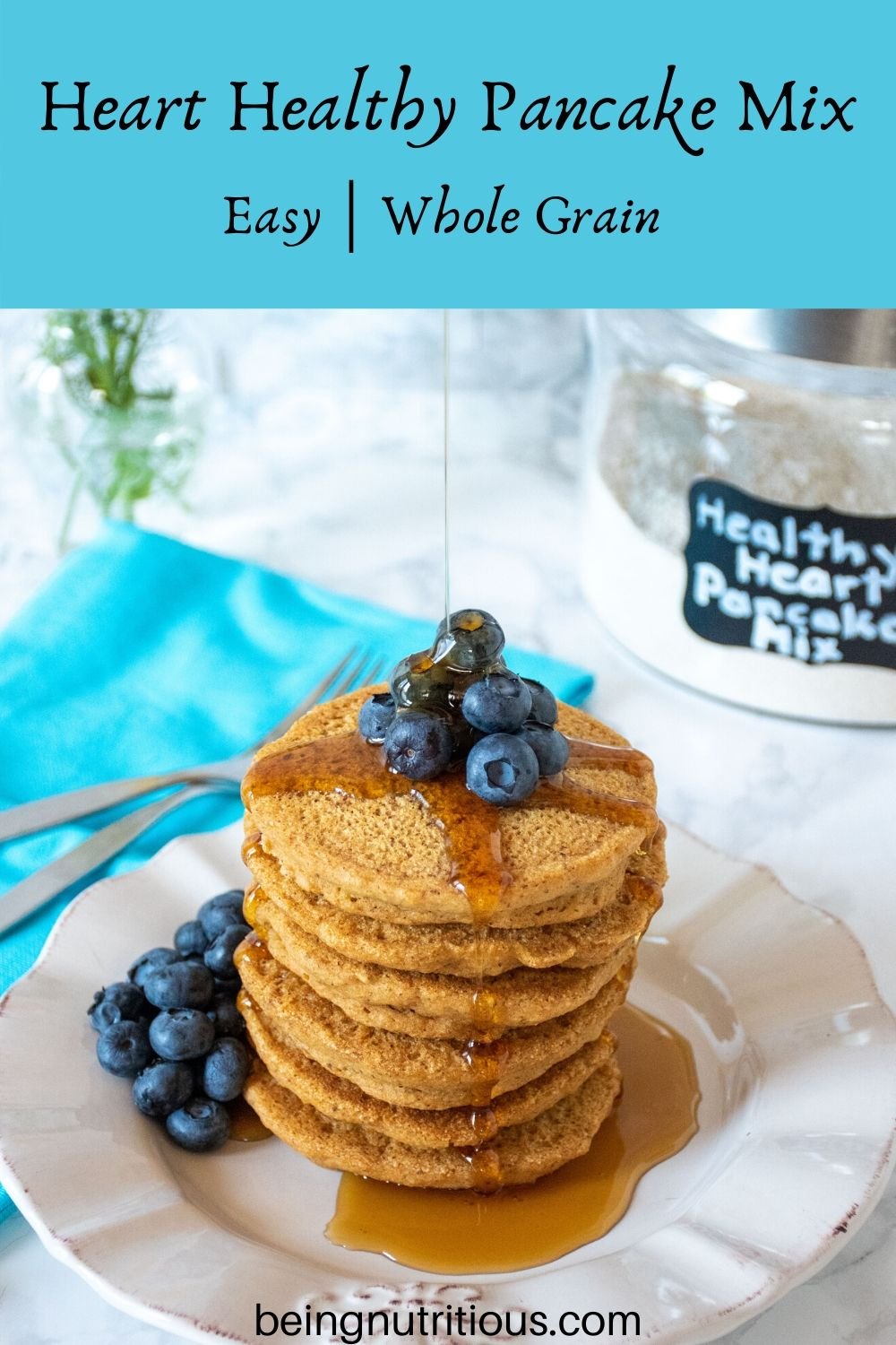 Stack of 6 whole wheat pancakes, with a pile of fresh blueberries on top, and syrup being poured over. Glass jar that reads 'healthy heart pancake mix' is visible in the background.