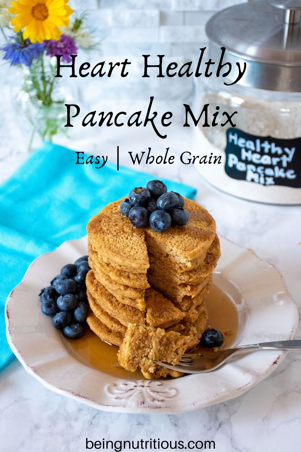 Stack of 6 whole wheat pancakes, with a pile of fresh blueberries on top, and syrup poured over. A fork with cut pieces of pancakes on it lies in front of the stack. Glass jar that reads 'healthy heart pancake mix' is visible in the background with a bouquet of flowers.
