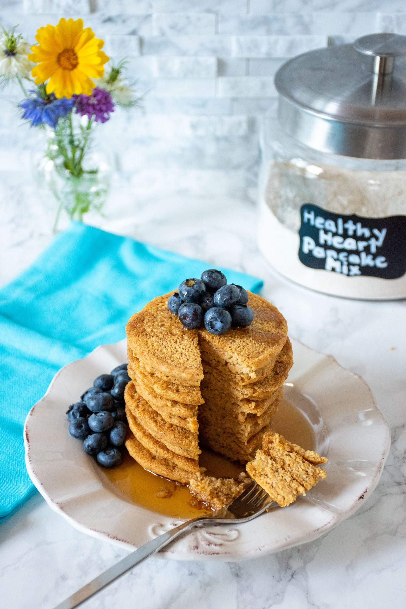 Stack of 6 whole wheat pancakes, with a pile of fresh blueberries on top, and syrup poured over. A fork with cut pieces of pancakes on it lies in front of the stack. Glass jar of heart healthy pancake mix is visible in the background with a bouquet of flowers.