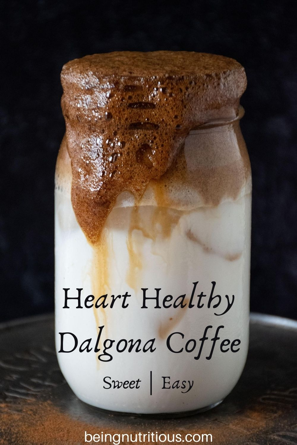 """Whipped coffee over iced almond milk in a Mason jar with streams of coffee running down the side of the jar. Text overlay: &quote;Heart Healthy Dalgona Coffee, sweet; easy"""""""