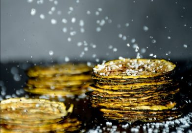 Square image of 3 stacks of zucchini chips, with salt crystals falling all around.