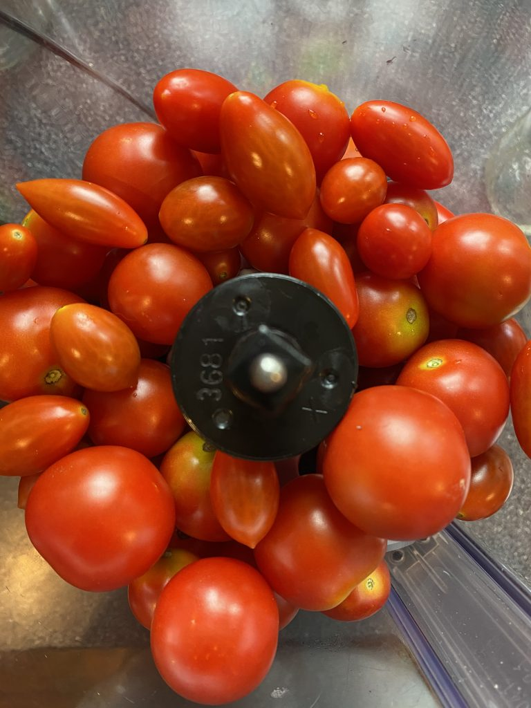 Whole cherry and grape tomatoes in a food processor.
