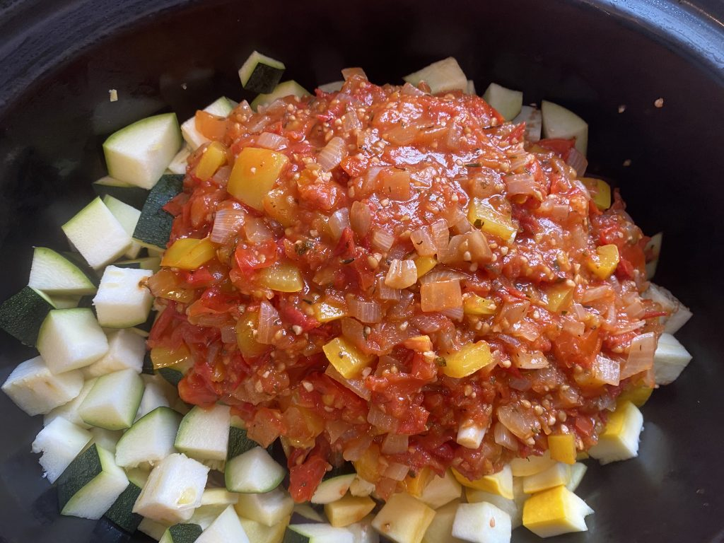 Diced veggies in a slow cooker, with ratatouille sauce poured over.