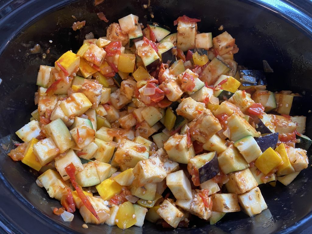 Diced veggies in a slow cooker mixed with sauce.
