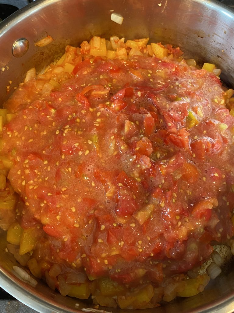 Diced tomatoes added to pan of sauteing peppers and onions.