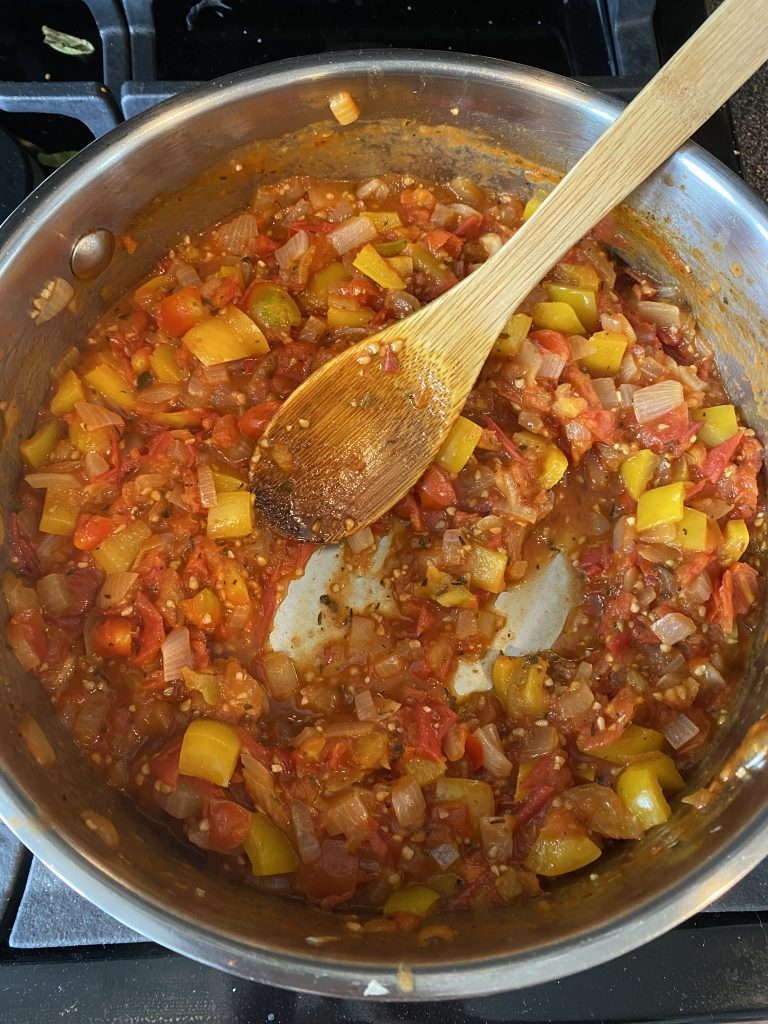 Reducing the ratatouille sauce in a pot until it's thickened.