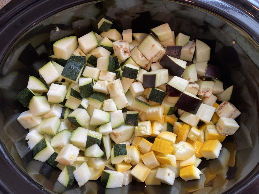 Diced eggplant, zucchini, and yellow squash in a slow cooker.