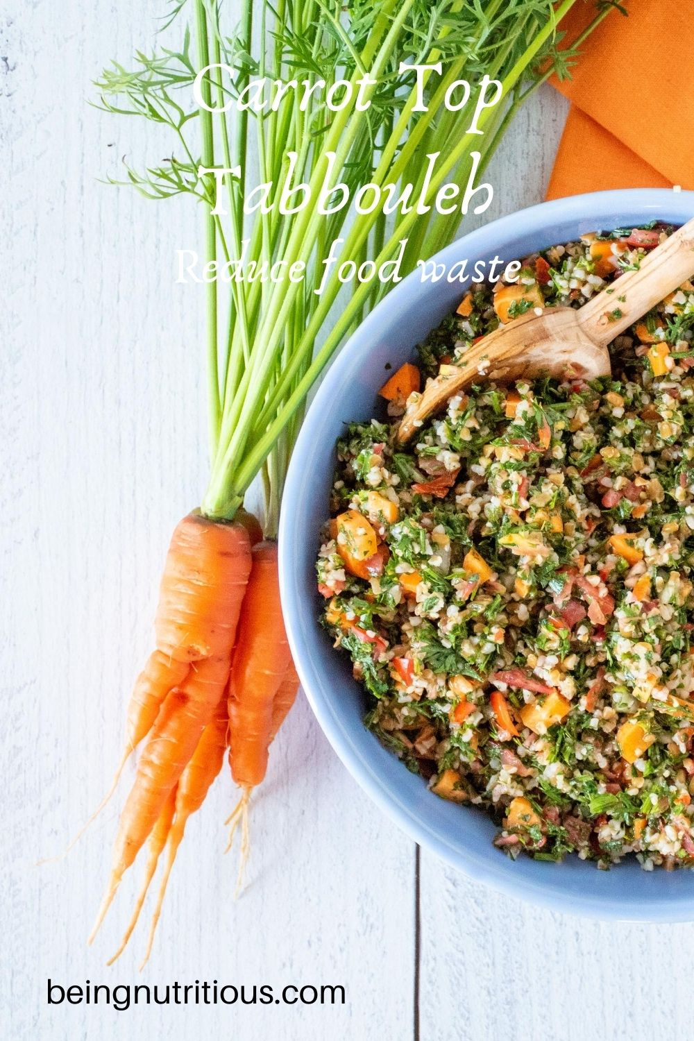 Overhead shot of carrot top tabbouleh in a blue bowl, half of the bowl shown, with a bunch of carrots with the tops still attached lying beside the bowl. Text overlay: Carrot Top Tabbouleh; Reduce food waste.