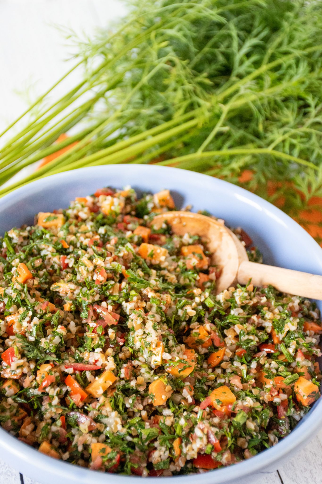Close up of tabbouleh in blue bowl, with carrot tops visible in background.