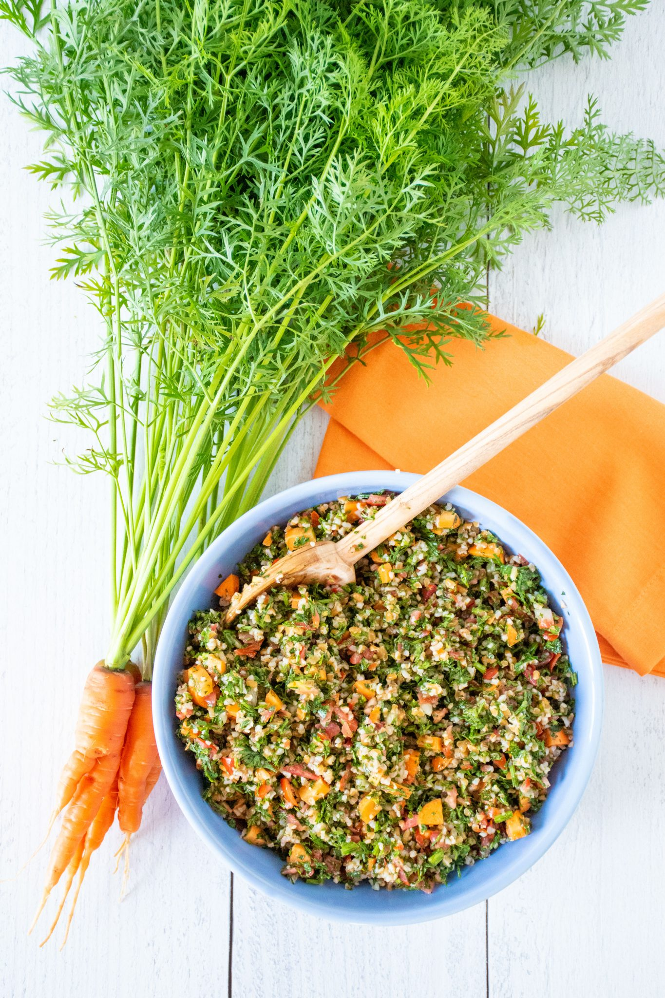Overhead shot of carrot top tabbouleh in a blue bowl, with a bunch of carrots with the tops still attached lying beside the bowl