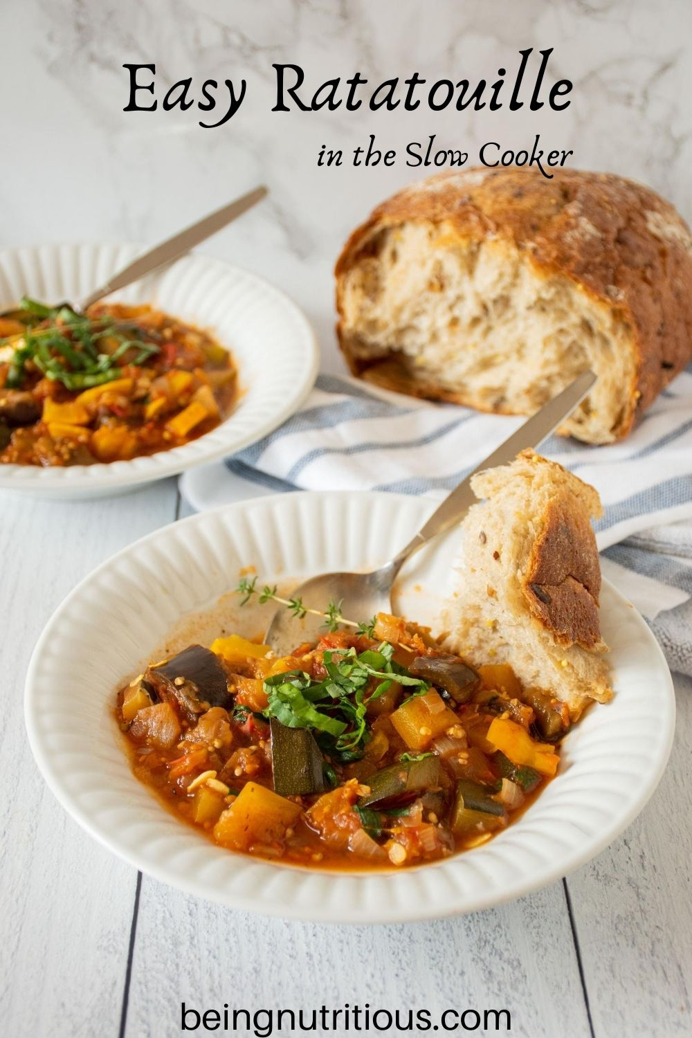 Bowl of ratatouille with rustic piece of bread. Another bowl and loaf of bread visible in background. Text overlay: Easy Ratatouille in the Slow Cooker.
