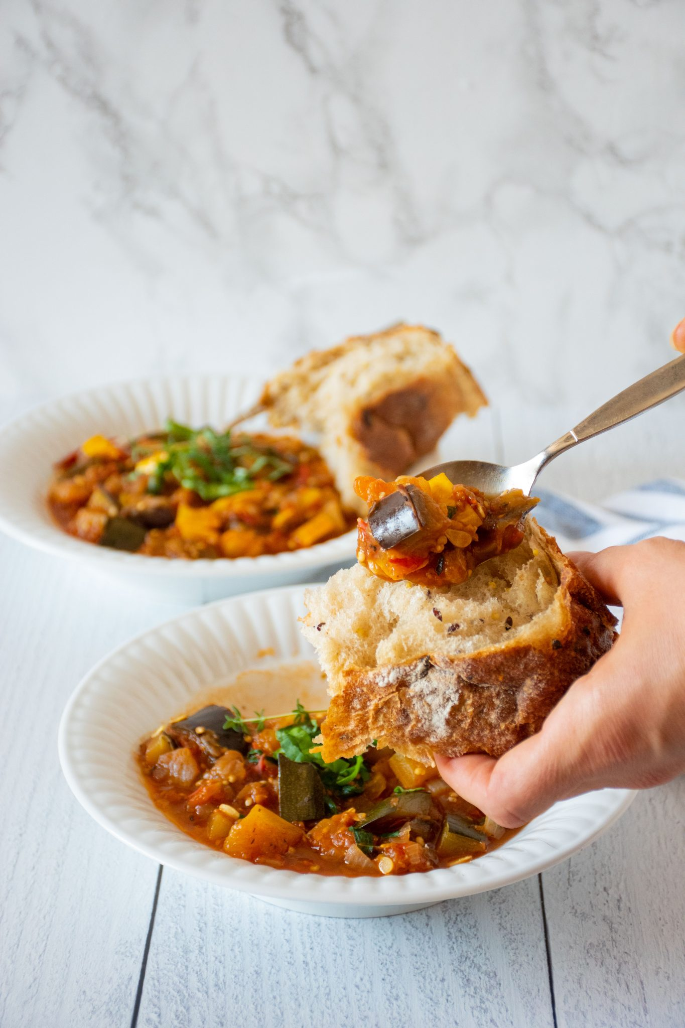 Hand holding a rustic piece of bread, spooning ratatouille on it. 2 bowls of ratatouille in background.