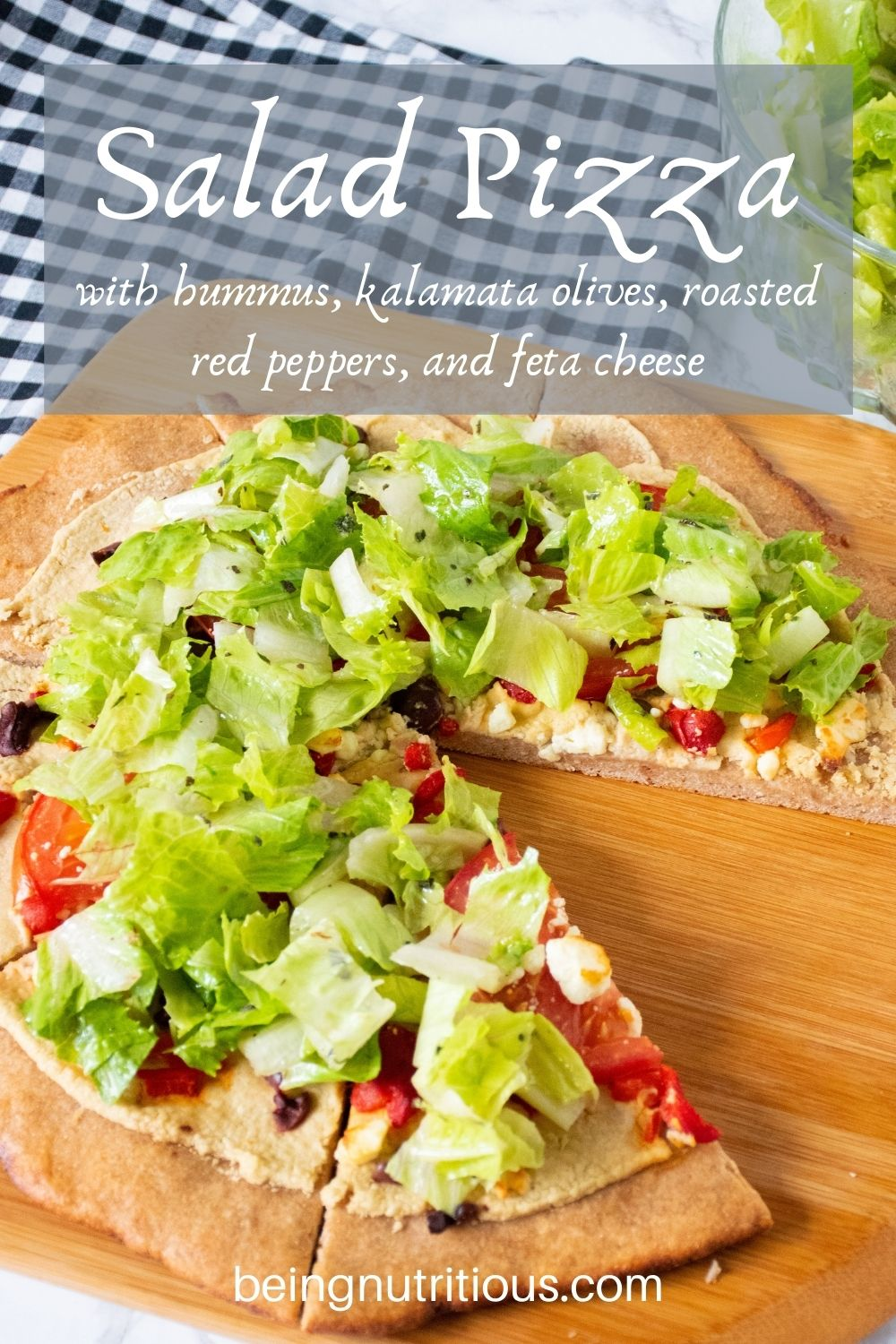 Pizza on a peel, with whole wheat crust, topped with salad. Text overlay: Salad Pizza with hummus, kalamata olives, roasted red peppers, and feta cheese.