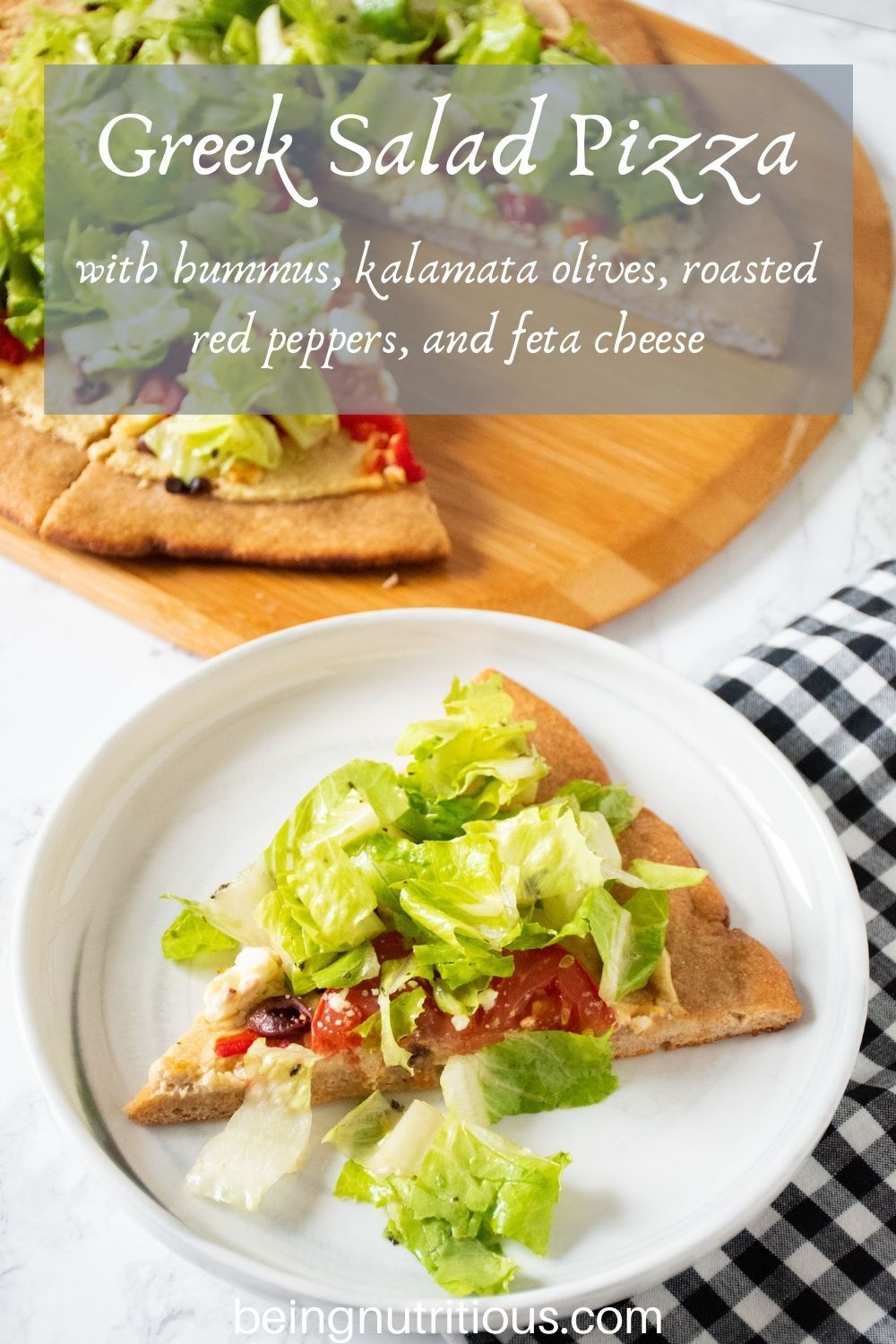 Slice of pizza on a plate. In background is the rest of the pizza on a peel, with whole wheat crust, topped with salad. Text overlay: Greek Salad Pizza with hummus, kalamata olives, roasted red peppers, and feta cheese.