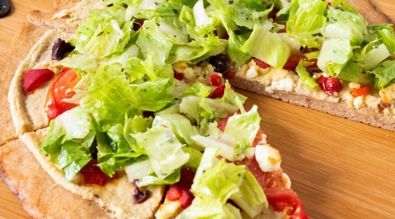 Pizza on a peel, with whole wheat crust, topped with salad.