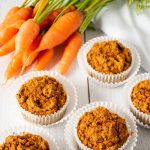 5 muffins on a table with fresh carrots.