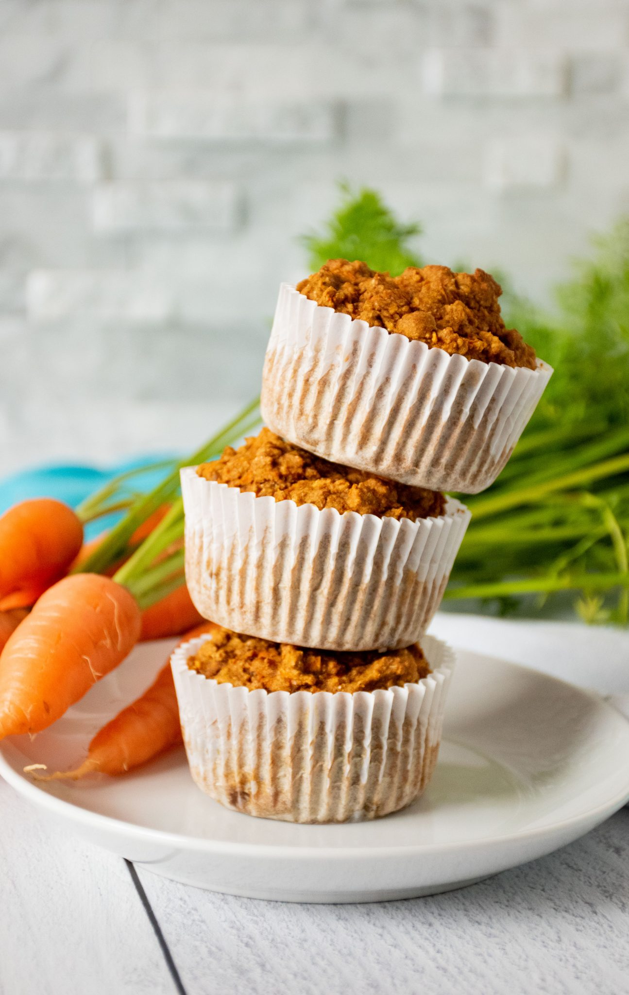 Stack of 3 muffins on a plate with fresh carrots in the background.