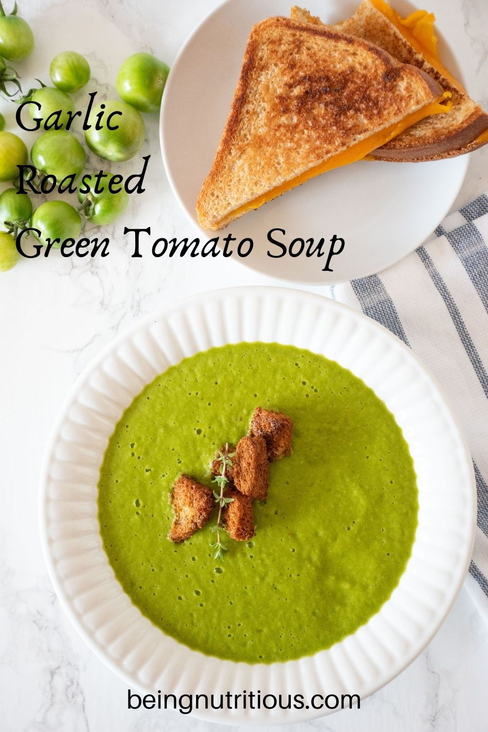 Overhead shot of green soup in a bowl with homemade croutons. Grilled cheese sandwich on a plate behind. Text overlay: Garlic Roasted Green Tomato Soup.