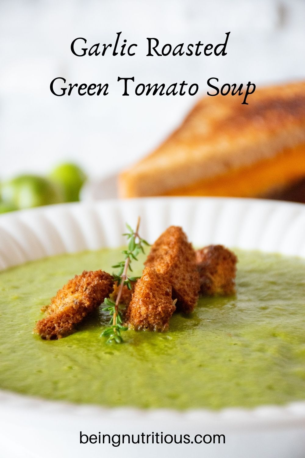Closeup shot of green soup in a bowl with homemade croutons. Text overlay: Garlic Roasted Green Tomato Soup.