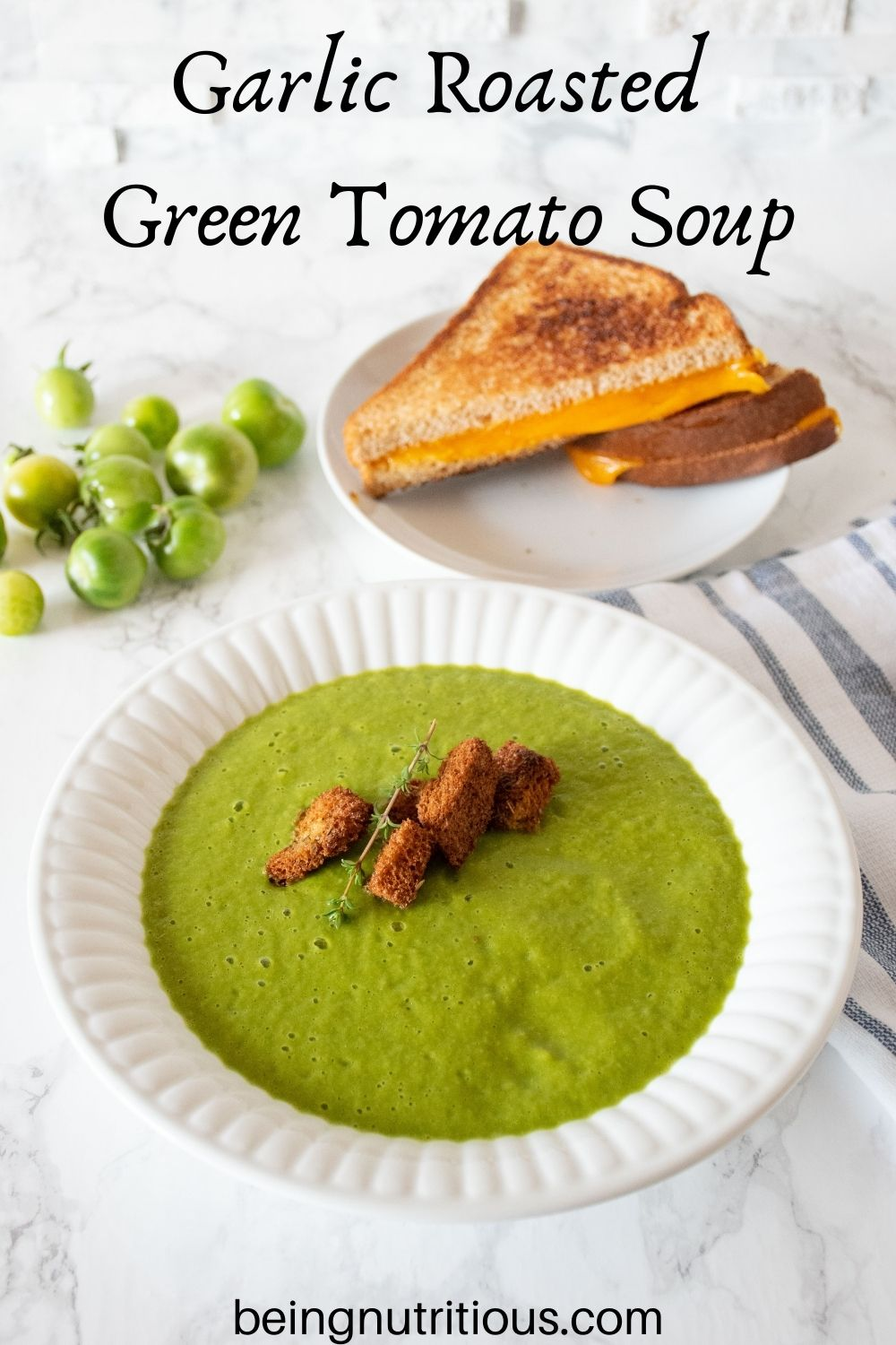 Green soup in a bowl with homemade croutons. Plate with grilled cheese sandwich in background. Text overlay: Garlic Roasted Green Tomato Soup.