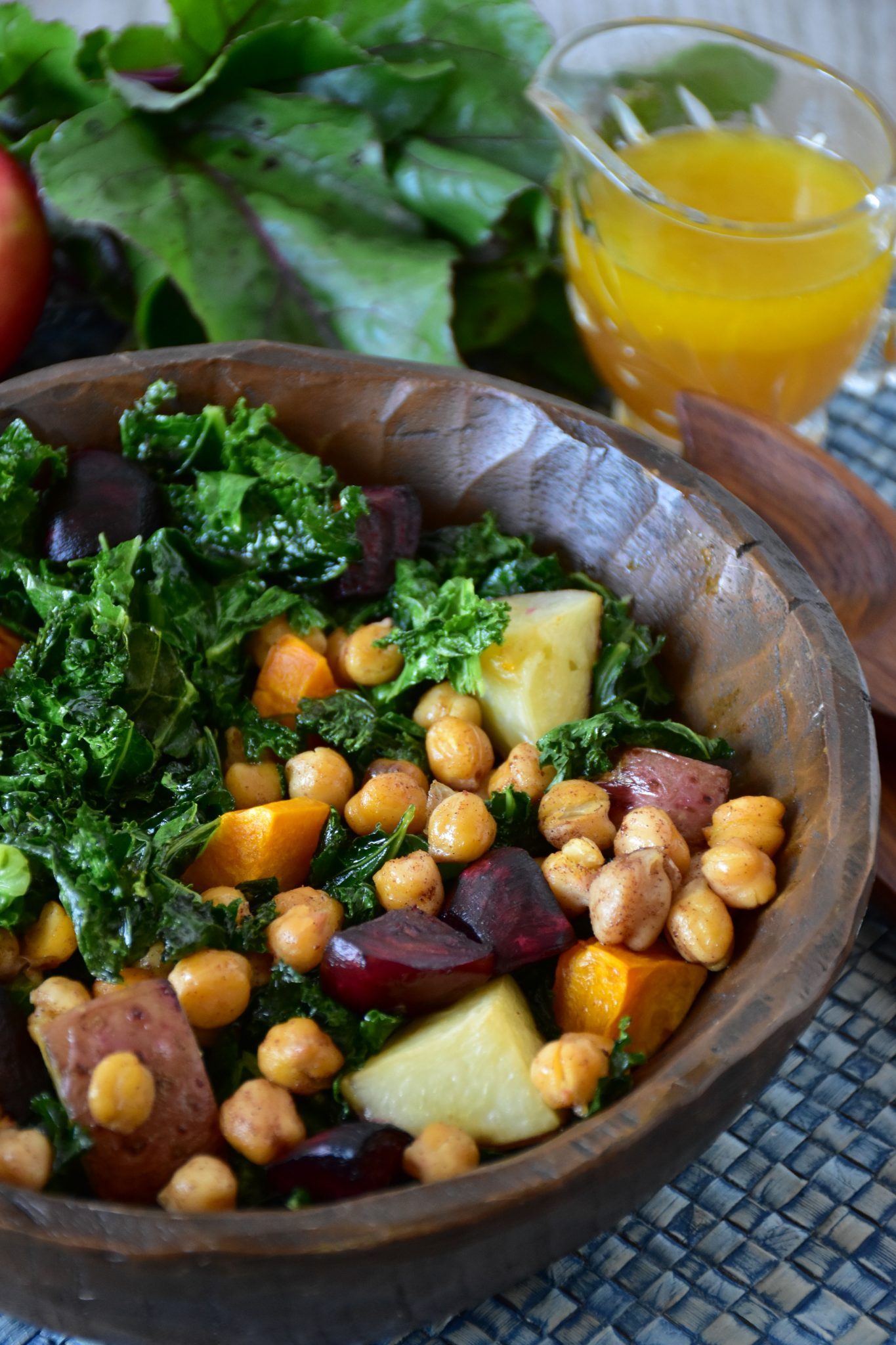 Kale salad in a wooden bowl with apple maple vinaigrette in the background.