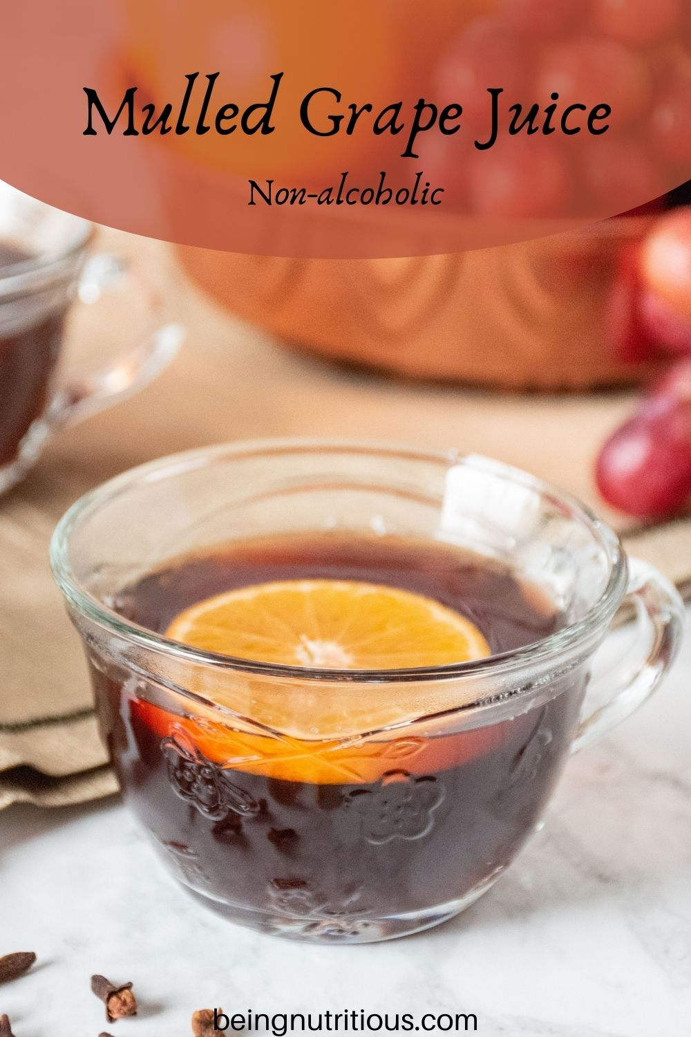 Close up of a small glass mug, filled with mulled grape juice, with an orange slice in it. Text overlay: mulled grape juice; non-alcoholic.