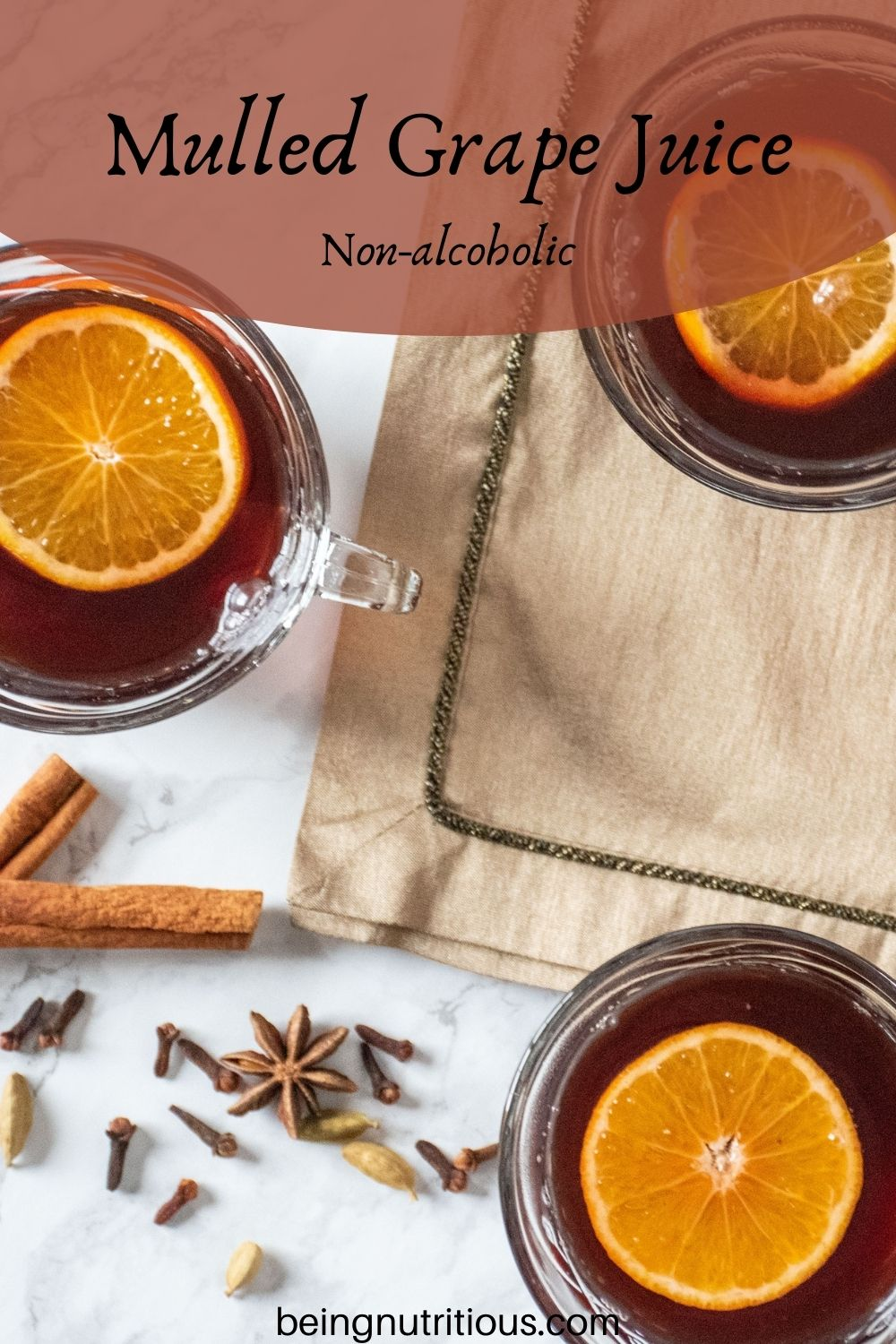 Overhead shot of 3 small glass mugs filled with mulled grape juice, each with an orange slice in them. Text overlay: Mulled Grape Juice; non-alcoholic.