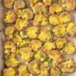 Overhead picture of smashed potatoes on a baking sheet.