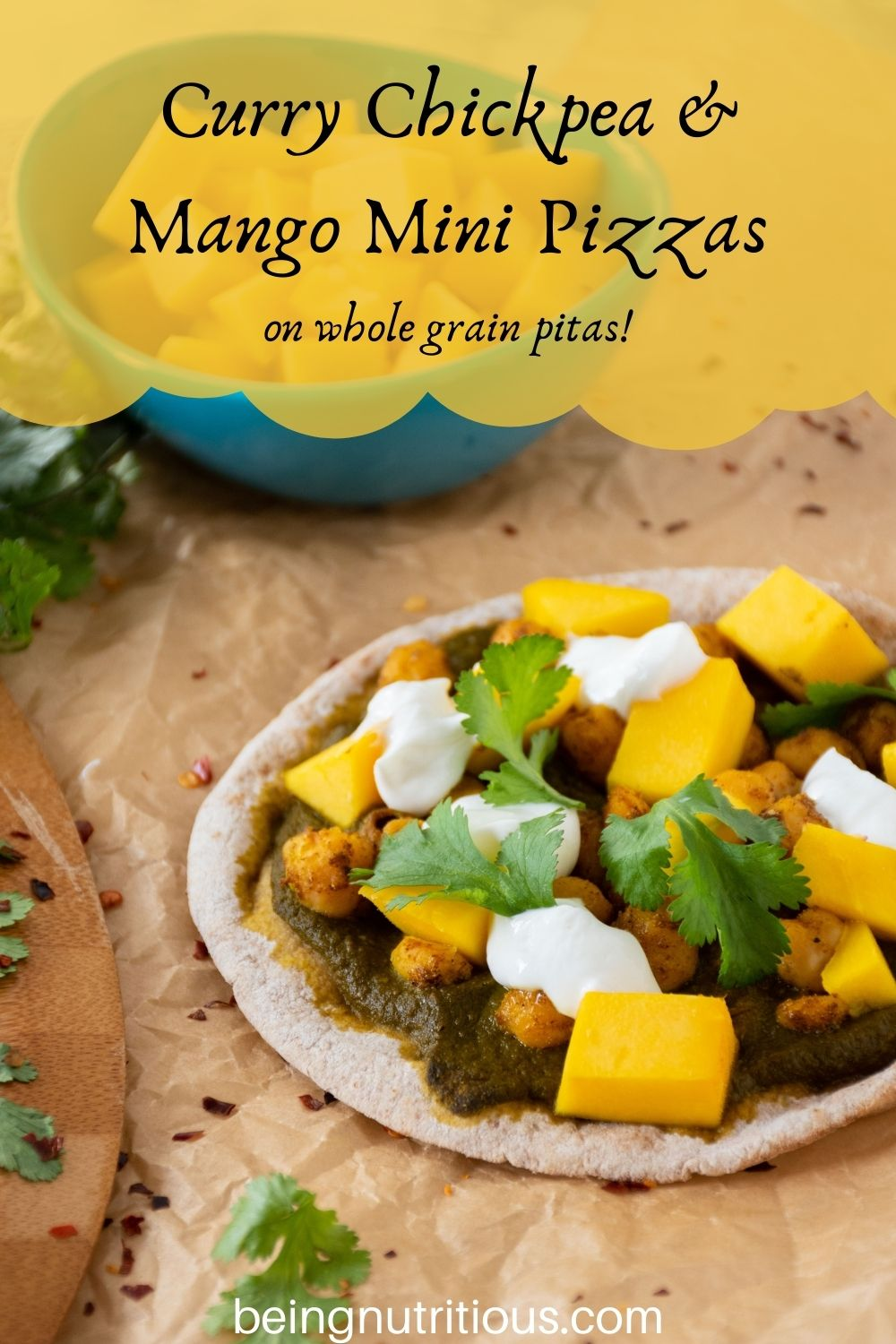 pizza with spinach sauce, chickpeas, and mangoes on a mini pita. Text overlay: Curry Chickpea & mango mini pizzas; on whole grain pitas!