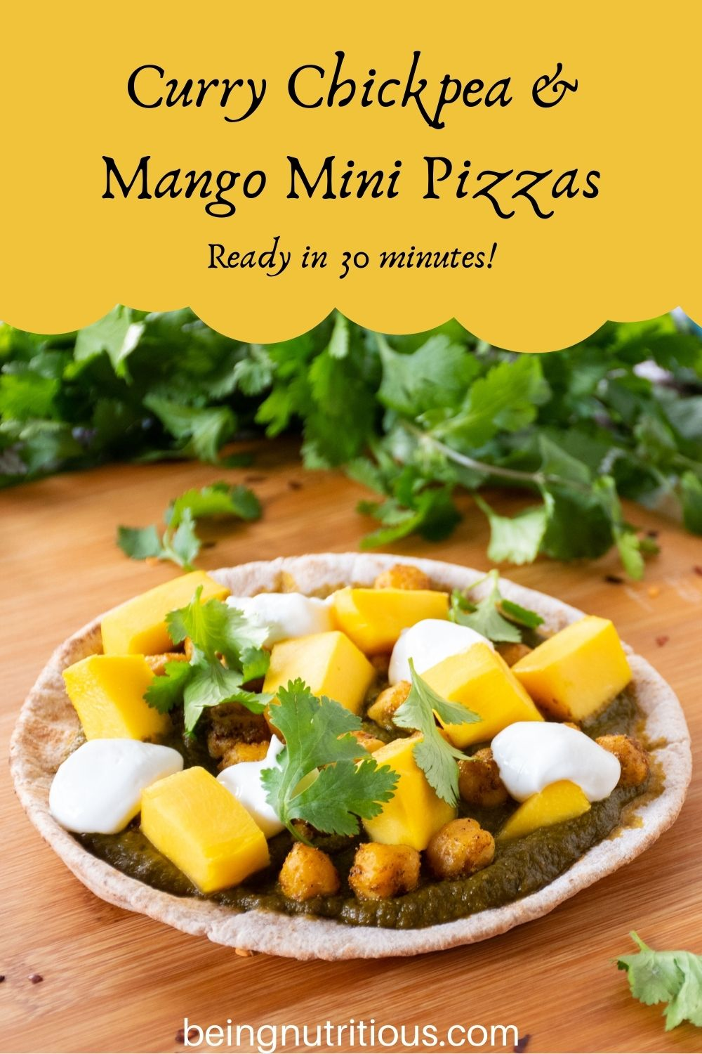 pizza with spinach sauce, chickpeas, and mangoes on a mini pita. Text overlay: Curry Chickpea & mango mini pizzas; ready in 30 minutes!